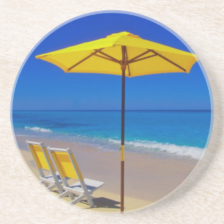 Yellow beach umbrella and chairs on pristine coaster