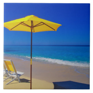 Yellow beach umbrella and chairs on pristine large square tile