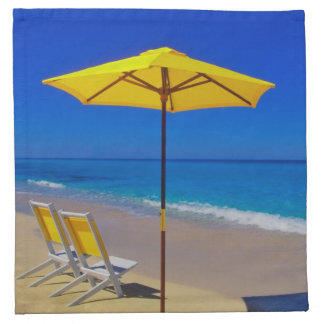 Yellow beach umbrella and chairs on pristine napkin