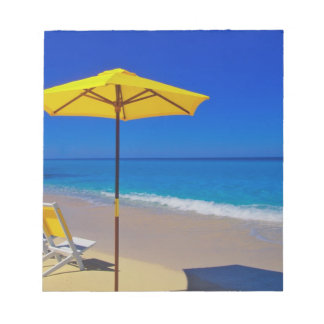 Yellow beach umbrella and chairs on pristine notepad