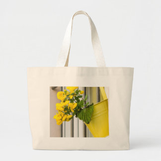 yellow flowers on the balcony large tote bag