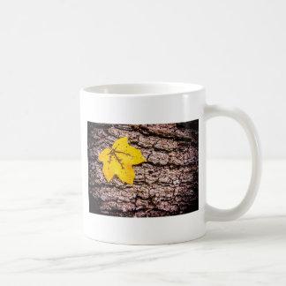 Yellow leaf against bark coffee mugs