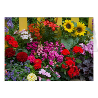 Yellow picket fence with flower garden in card