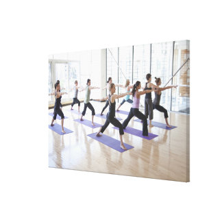 Yoga instructor teaching a class of women the stretched canvas print
