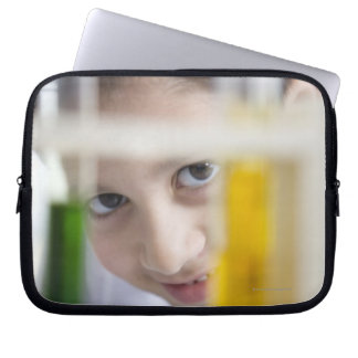 Young boy in chemistry science class, looking laptop sleeve