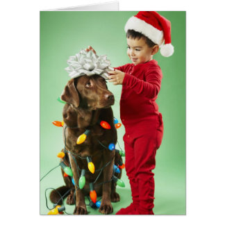 Young boy wrapping Christmas lights around a dog Card