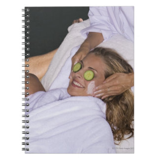 Young couple enjoying a spa treatment. spiral notebook