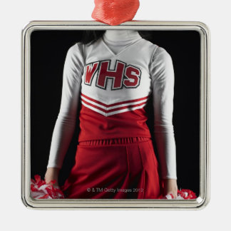 Young female cheerleader holding pom-poms, mid christmas ornament