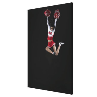 Young female cheerleader jumping in midair, arms 2 canvas print