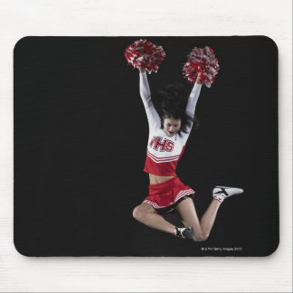 Young female cheerleader jumping in midair, arms 2 mouse mat