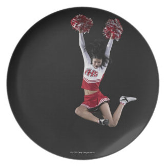 Young female cheerleader jumping in midair, arms 2 plate