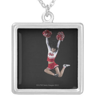 Young female cheerleader jumping in midair, arms 2 silver plated necklace