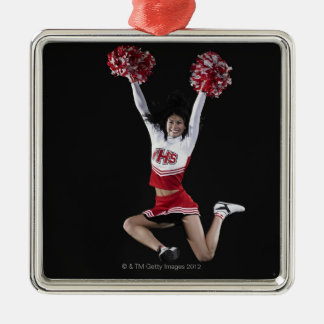 Young female cheerleader jumping in midair, arms Silver-Colored square decoration