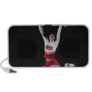 Young female cheerleader jumping in midair, arms travel speakers