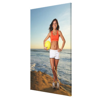 young fit pretty female holding a volleyball at canvas print