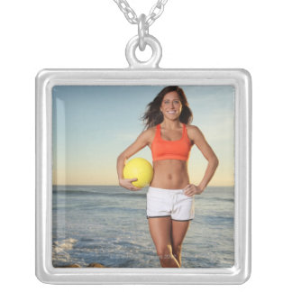 young fit pretty female holding a volleyball at silver plated necklace