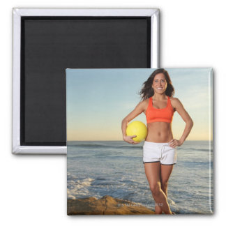 young fit pretty female holding a volleyball at square magnet