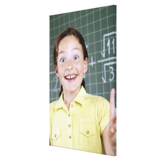 young girl in front of blackboard having idea canvas print