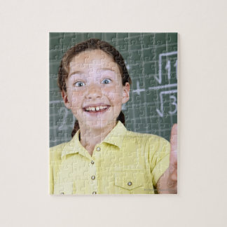 young girl in front of blackboard having idea jigsaw puzzle