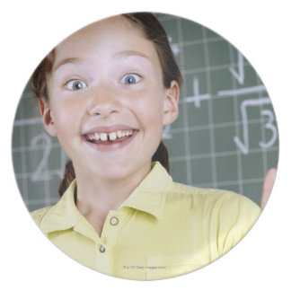 young girl in front of blackboard having idea plate