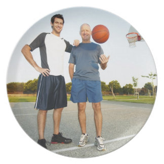 Young man and senior man on outdoor basketball plate