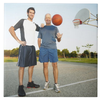 Young man and senior man on outdoor basketball tile