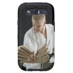 Young man breaking boards with karate chop on galaxy SIII covers