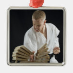 Young man breaking boards with karate chop on ornaments