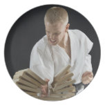 Young man breaking boards with karate chop on dinner plate