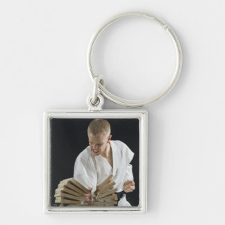 Young man breaking boards with karate chop on key ring