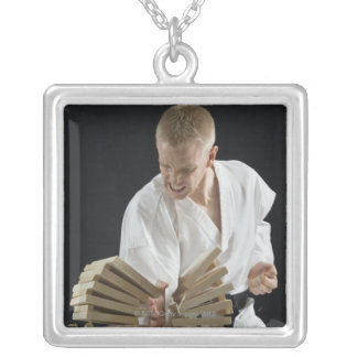 Young man breaking boards with karate chop on square pendant necklace