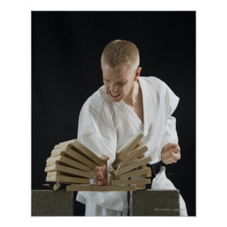 Young man breaking boards with karate chop on poster