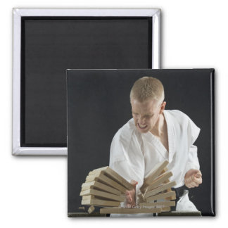 Young man breaking boards with karate chop on square magnet