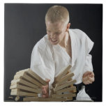 Young man breaking boards with karate chop on tiles
