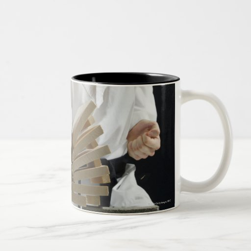 Young man breaking boards with karate chop on Two-Tone mug