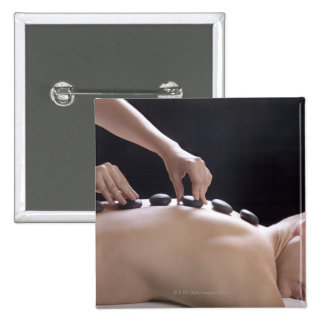 young man getting hot stone massage treatment 15 cm square badge