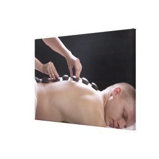young man getting hot stone massage treatment canvas print