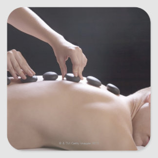 young man getting hot stone massage treatment square sticker
