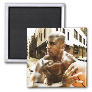 Young man holding basketball square magnet