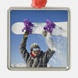 Young man holding his snowboard above his head christmas ornament