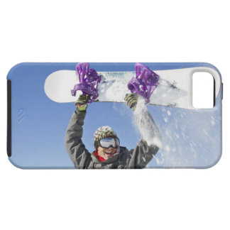 Young man holding his snowboard above his head iPhone 5 cases
