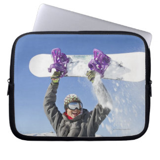 Young man holding his snowboard above his head laptop sleeve