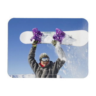 Young man holding his snowboard above his head magnet