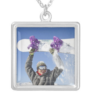 Young man holding his snowboard above his head silver plated necklace