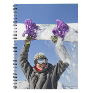 Young man holding his snowboard above his head spiral notebook