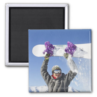 Young man holding his snowboard above his head square magnet