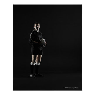 Young man holding rugby ball, portrait posters
