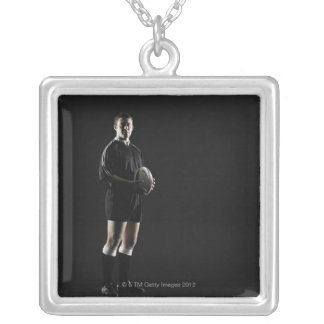 Young man holding rugby ball, portrait silver plated necklace
