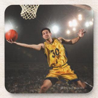 Young man jumping and holding basketball coaster