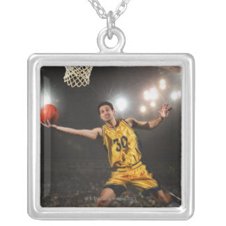 Young man jumping and holding basketball silver plated necklace